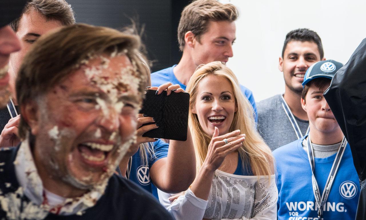 Als die Torte im Gesicht des Volkswagen Motorsport-Chefs landete, war sogar die Ehefrau von Rallye-Weltmeister Sebastien Ogier, Andrea Kaiser, überrascht.