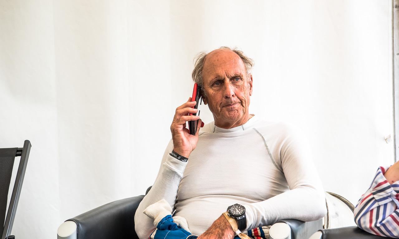 Hans-Joachim Stuck vor seinem Stint im Porsche 962 C schwer beschäftigt am Telefon. Wussten Sie, dass er mal Hausverbot im Kempinski in Berlin hatte? Hier lesen Sie warum.